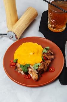 Grillowane szaszłyki z kurczaka i puree z dyni na białym talerzu.