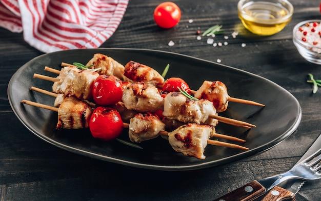 Grillowane szaszłyki z kurczaka z pomidorkami cherry na czarnym talerzu. czarny drewniany stół. selektywna ostrość