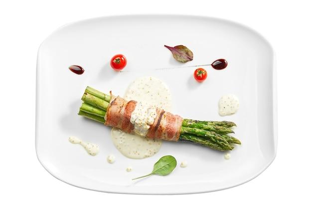 Grillowane szparagi z boczkiem i sosem musztardowym w białym talerzu. na białym tle na białej powierzchni. widok z góry