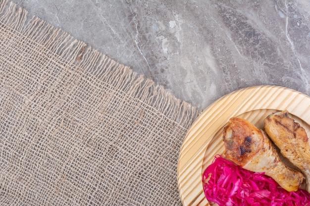 Grillowane udka z kurczaka i kapusta kiszona na drewnianym talerzu.
