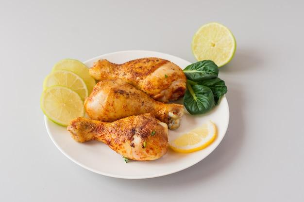 Grillowane udka z kurczaka i warzywa na białym stole
