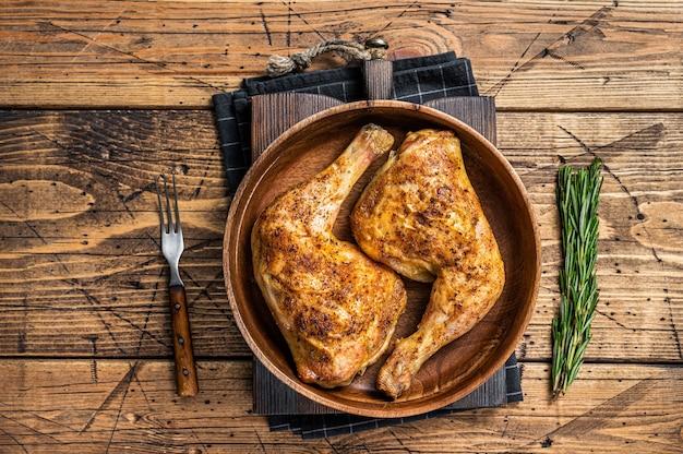 Grillowane udka z kurczaka na drewnianym talerzu z ziołami. drewniane tła. widok z góry.