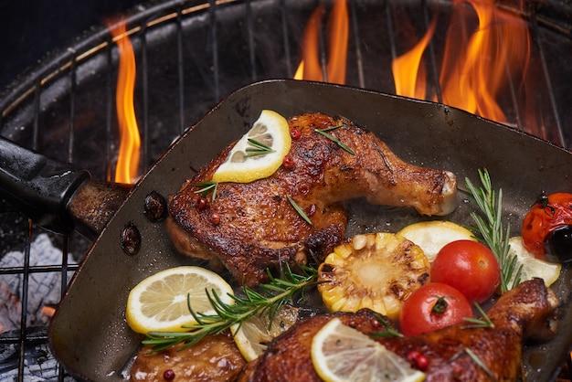 Grillowane udka z kurczaka na płonącym grillu z grillowanymi warzywami z pomidorami, ziemniakami, pieprzem, solą.