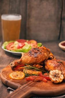 Grillowane udka z kurczaka pieczone na grillu na drewnianej desce do krojenia z sosem pomidorowym w misce, świeżymi pomidorami i liśćmi sałaty, gorzka papryka, szklany kufel piwa