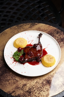 Grillowane udko z kaczki z polentą i sosem. pieczona kaczka udko na białym talerzu na stole