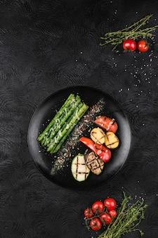 Grillowane warzywa na czarnym talerzu. szparagi, papryka, cukinia, bakłażan, ziemniaki i pomidory pieczone na ogniu.