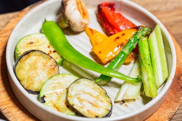 Grillowane warzywa w białym talerzu. papryka, grzyby, cukinia i szparagi z bliska.