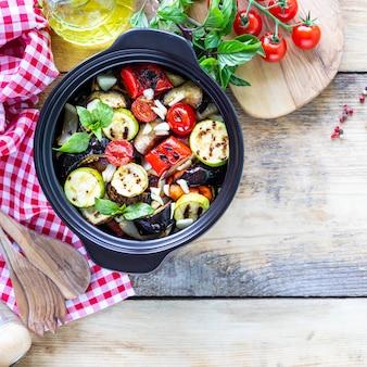 Grillowane warzywa w czarnej ceramicznej patelni na drewnianej powierzchni