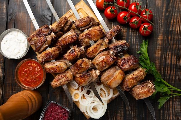 Grillowane żeberka jagnięce na desce do krojenia na szpikulcu z przyprawami i sosem. widok z góry na ciemny drewniany stół