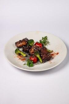 Grillowane żeberka wieprzowe w polewie miodowej z pomidorami i brokułami na białej powierzchni