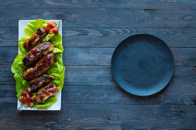 Grillowane żeberka wieprzowe z grilla z warzywami na drewnianej powierzchni; wolne miejsce przed tekstem.
