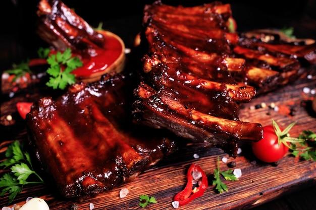 Grillowane żeberka wieprzowe z przyprawami i warzywami na drewnianym tle