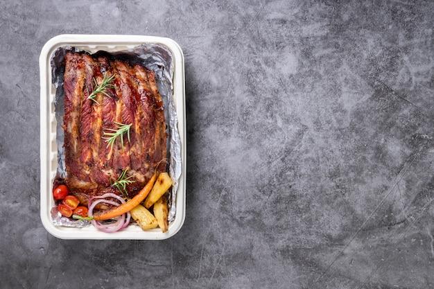 Grillowane żeberka wieprzowe z warzywami i sosami na stole drak