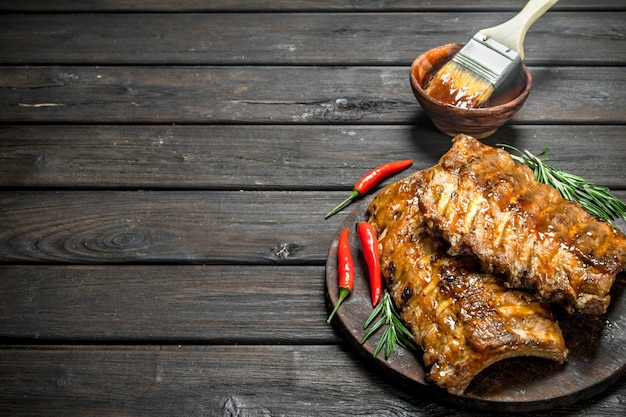 Grillowane żeberka z rozmarynem i ostrą papryczką chili. na drewnianym tle.