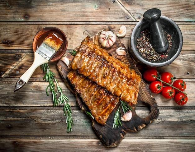 Grillowane żeberka z rozmarynem, przyprawami i sosem. na drewnianym tle.