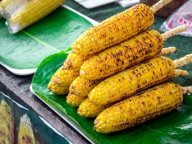 Grillowane ziarna na zielonym liściu bananowca, uliczne jedzenie gotowe do podania. grillowane warzywa, dania wegetariańskie, kukurydza bbq.