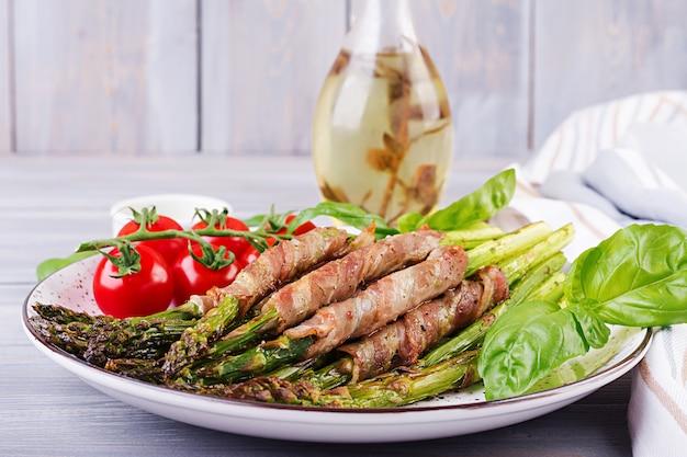 Grillowane zielone szparagi owinięte boczkiem na drewnianym stole.