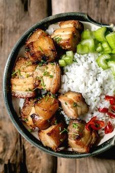 Grillowany boczek wieprzowy smażony w misce z ryżem, selerem, papryczką chili i szczypiorkiem na stare drewniane tła. leżał płasko, kopia przestrzeń
