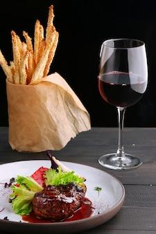 Grillowany filet mignon z sałatką z warzyw i kieliszkiem czerwonego wina i grissini z bliska. talerz z filetem mignon na drewnianym stole