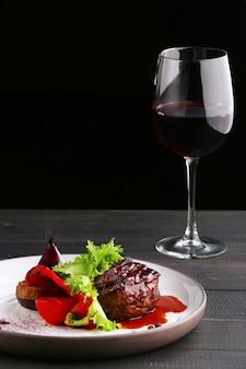 Grillowany filet mignon z sałatką z warzyw i kieliszkiem czerwonego wina z bliska. talerz z filetem mignon na drewnianym stole i czarnym stole