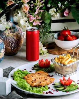Grillowany filet rybny podawany z frytkami, ogórkiem i pomidorem