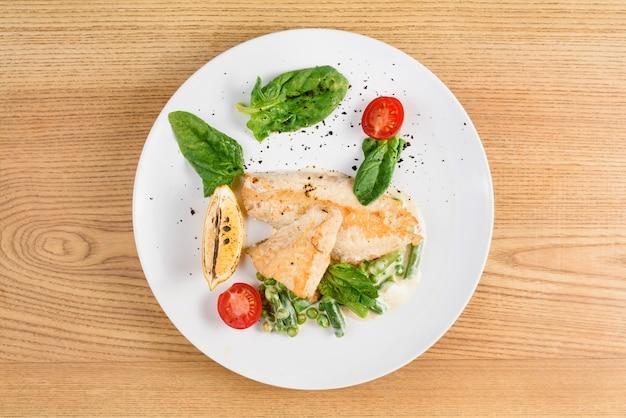Grillowany filet z kurczaka z bazylią, pomidorkami koktajlowymi, cytryną, groszkiem, sosem na białym okrągłym talerzu na drewnianym stole