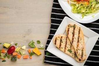 Grillowany filet z kurczaka z sałatką i rozrzuconymi kawałkami warzyw na drewnianym biurku