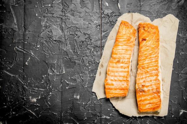 Grillowany filet z łososia na papierze. na czarnym tle rustykalnym.