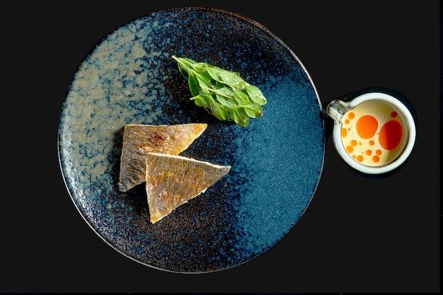 Grillowany filet z okonia morskiego ze szpinakiem i żółtym sosem w ceramicznym talerzu. dostawa jedzenia. pojedynczo na czarno