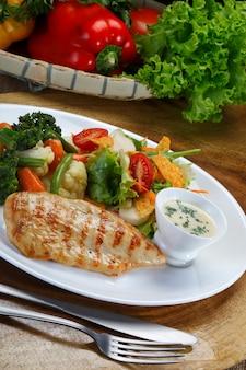 Grillowany filet z piersi kurczaka z surówką, gotowanymi warzywami i białym sosem
