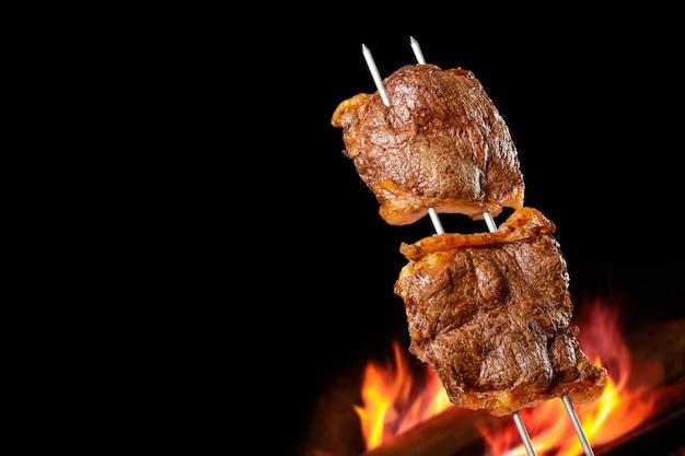 Grillowany grill picanha z rozmytym ogniem w tle zwany także churrasco