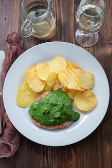 Grillowany hamburger z zielonym sosem i frytkami na białym talerzu