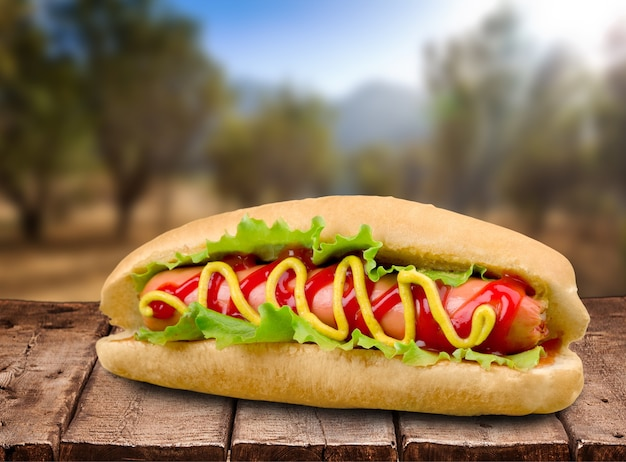 Grillowany hot dog z żółtą musztardą na tle