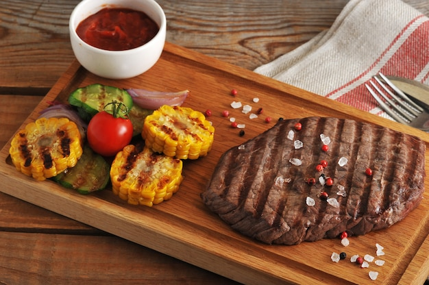 Grillowany kawałek wołowiny z krystaliczną solą, pieprzem i grillowaną kukurydzą