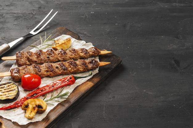 Grillowany kebab lula na szaszłykach podany na drewnianej desce, czarny stół