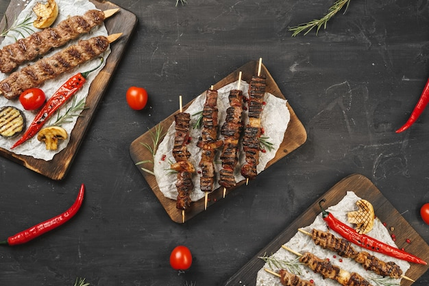 Grillowany kebab lula na szaszłykach podawany na desce, tło czarny stół