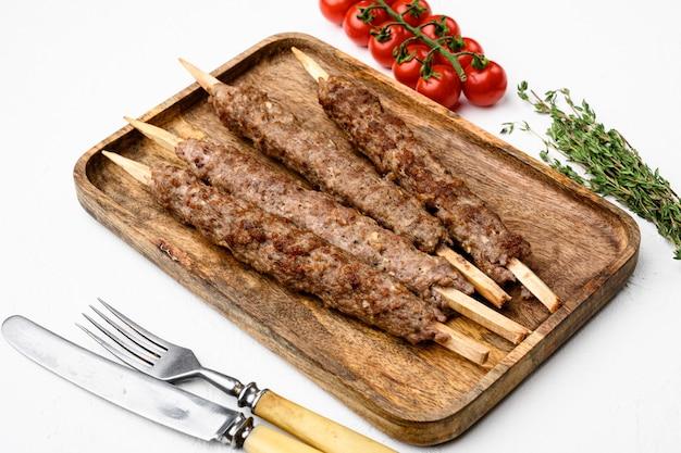 Grillowany kebab lula na szaszłykach z zestawem przypraw, na białym tle kamiennego stołu