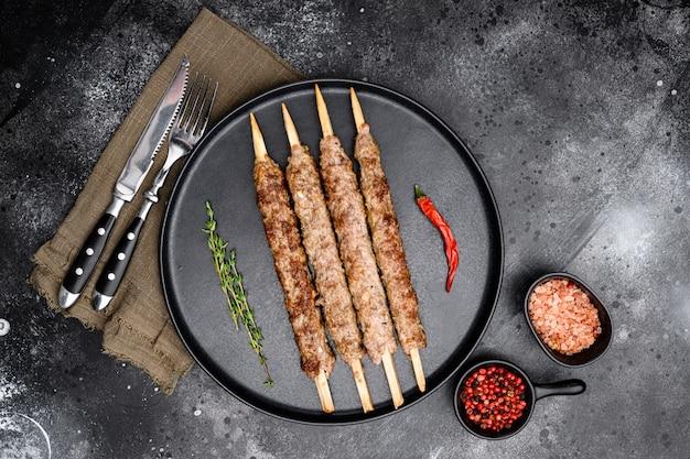Grillowany kebab lula na szaszłykach z zestawem przypraw, na talerzu, na czarnym ciemnym tle kamiennego stołu, widok z góry płasko leżący