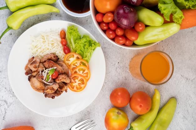 Grillowany kotlet wieprzowy z pomidorami i sałatką, ułożony w białym naczyniu.