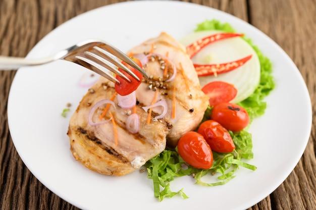 Grillowany kurczak na białym talerzu z pomidorami, sałatką, cebulą, chili i sosem.