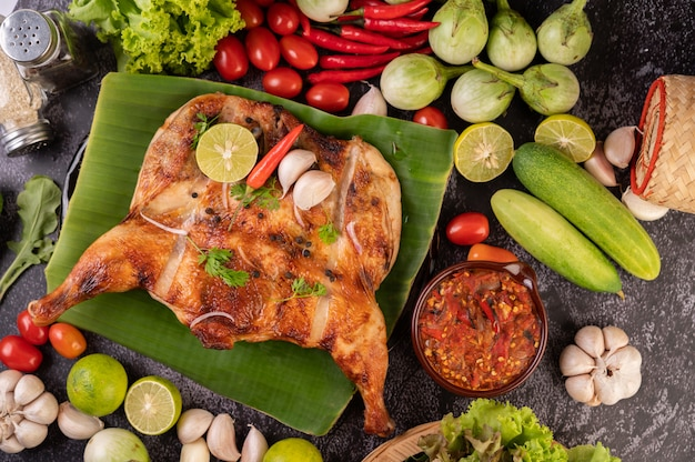 Grillowany kurczak na talerzu z papryczkami chili, sosem czosnkowym i posypany pestkami pieprzu.