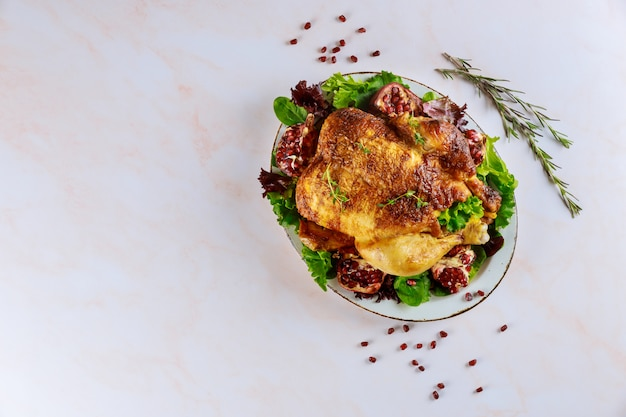 Grillowany kurczak na talerzu z zieloną sałatą i granatem