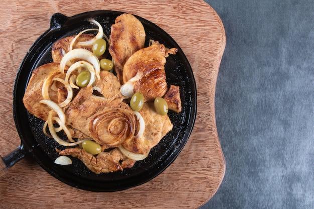 Grillowany kurczak z cebulą i oliwkami na widoku z góry żelaznej płyty.
