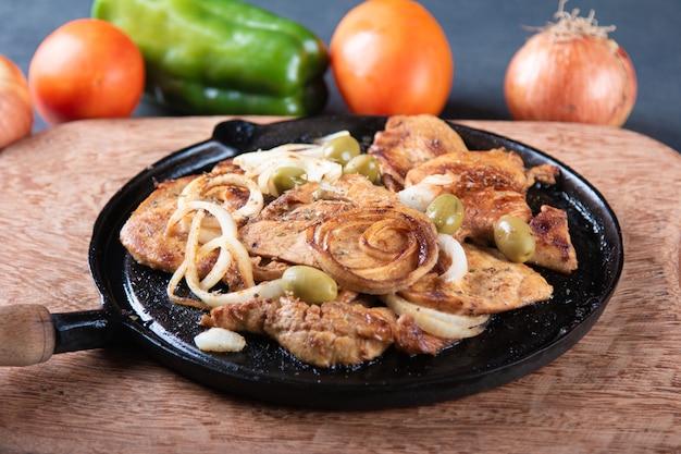 Grillowany kurczak z cebulą i oliwkami na żelaznym talerzu.