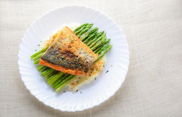 Grillowany łosoś przyozdobiony szparagami, ziołami i puree ziemniaczanym, podawany na białym talerzu.