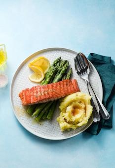 Grillowany łosoś ze świeżymi szparagami i puree ziemniaczanym na talerzu. zdrowe jedzenie na stole