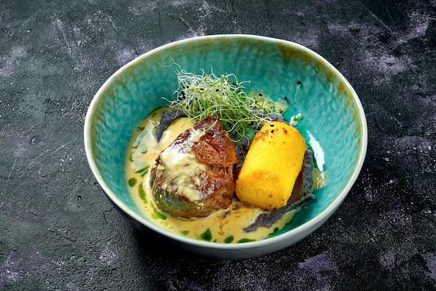 Grillowany mignon filet z sosem grzybowym i polentą w niebieskiej misce na czarnej powierzchni