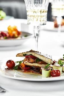 Grillowany okoń morski z smażonymi pomidorami, podawany z kulką ziemniaczaną na białym talerzu, zarys fileta z okonia morskiego na jasnym tle