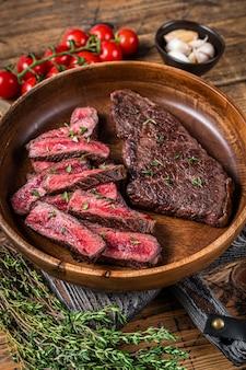 Grillowany pokrojony górny stek lub stek z wołowiny denver w drewnianym talerzu z ziołami. drewniane tła. widok z góry.