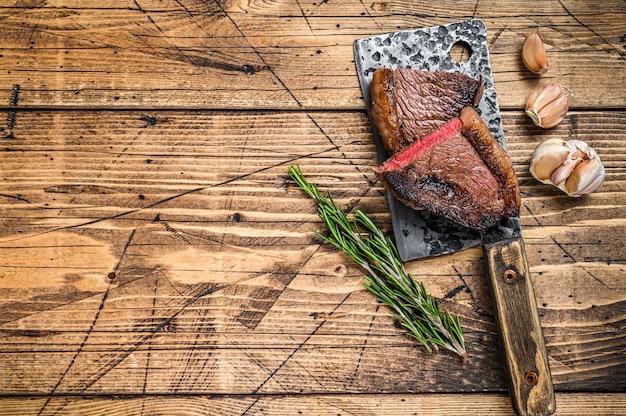 Grillowany rumsztyk lub brazylijski stek wołowy picanha na tasaku. drewniane tła. widok z góry. skopiuj miejsce.